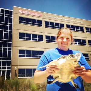 Dr. Emily Christiansen outside CMAST with a Kemp's Ridley Sea Turtle