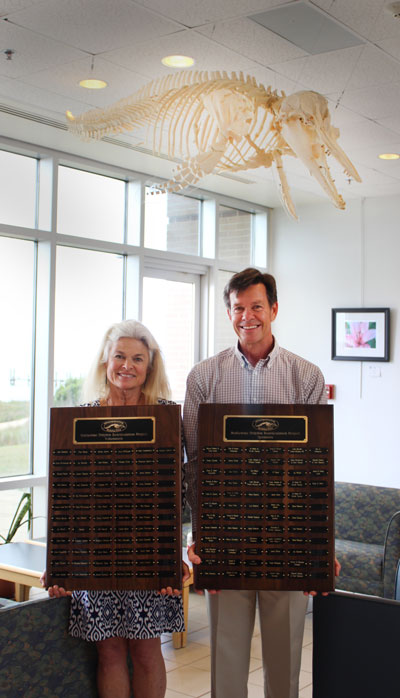 Dr. Vicky Thayer, Skeleton Crew Rearticulation Project Coordinator, and Dr. David Eggleston, Director of CMAST display donor plaques beneath the new dolphin skeleton on display.